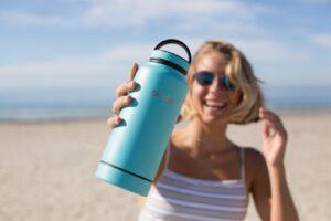 Women on beach hold water bottle
