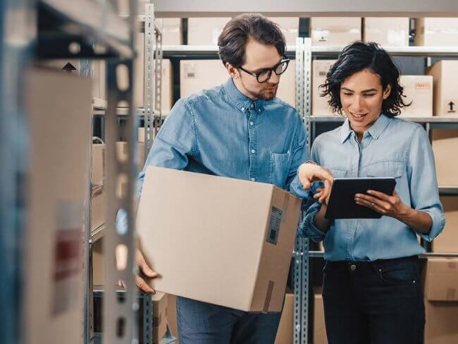 Women holding tablet while man hold box in warehouse